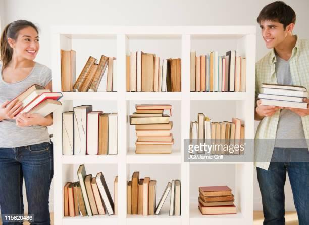 Couple with books standing near bookshelf