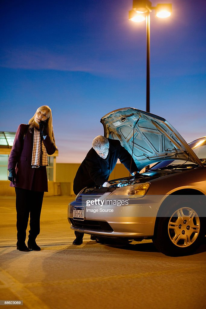 Couple with broken down car : Stock Photo