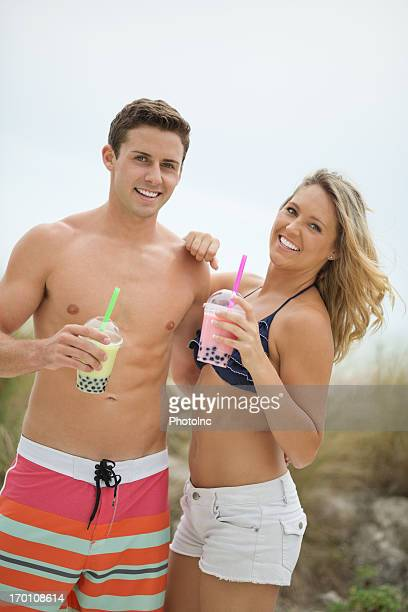 Couple With Bubble Teas Standing Together At Beach