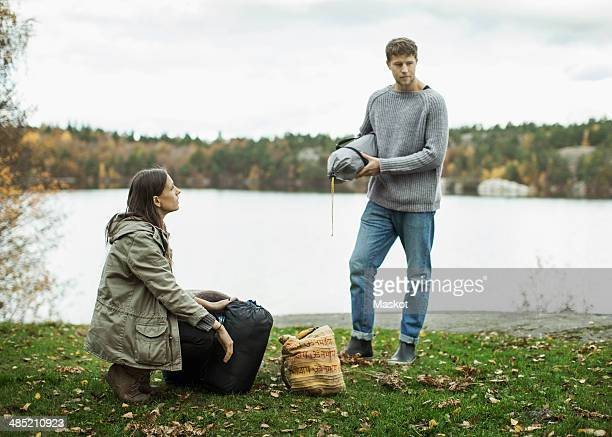 Couple with camping luggage on lakeshore