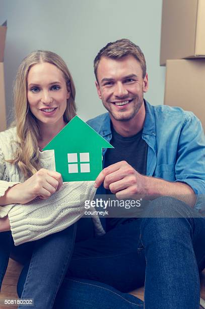 Couple with cardboard moving boxes and house symbol