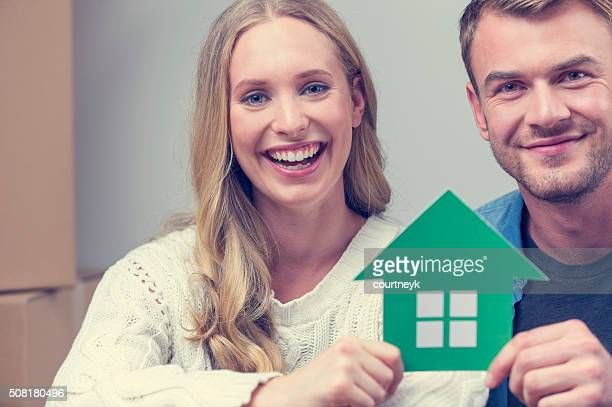 Couple with cardboard moving boxes and house symbol.