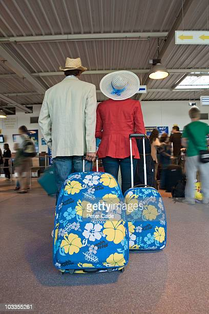 couple with cases in airport check-in queue