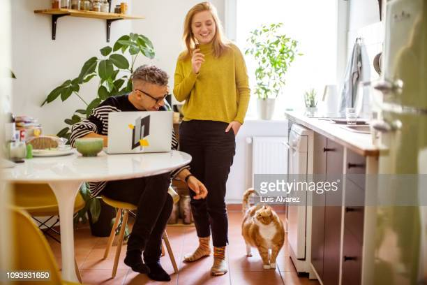 couple with cat at home - domestic animals stock pictures, royalty-free photos & images