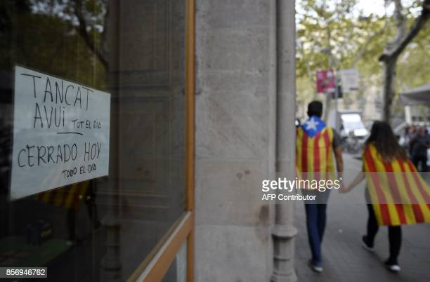 A couple with Catalan flags walk past a note on a shopwindow reading in Catalan and Spanish 'Closed today all day' during a general strike called by...