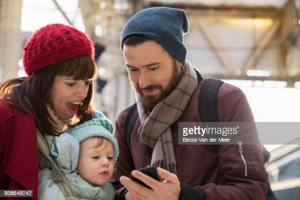 Couple with child look at mobilephone in railroad station.