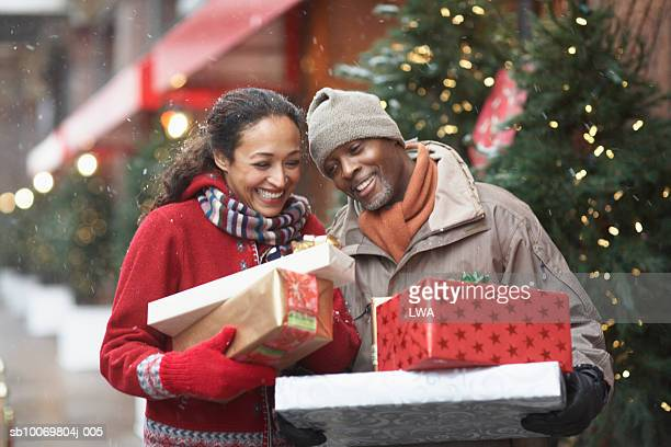 couple with christmas presents on street - african american christmas images stock pictures, royalty-free photos & images