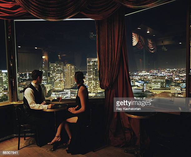 Couple with cocktails overlooking cityscape