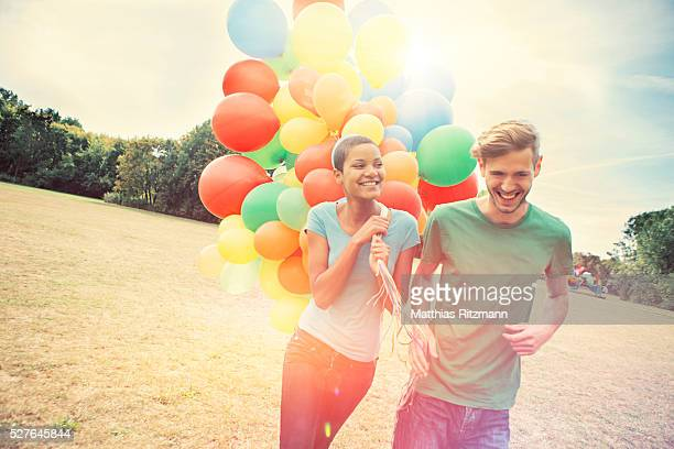 Couple with colorful balloons walking in park
