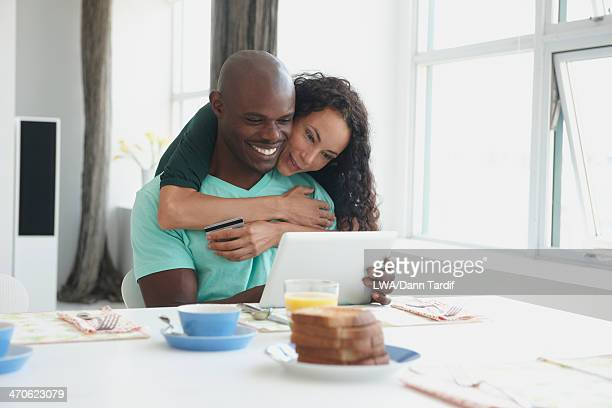 Couple with digital tablet hugging at breakfast table