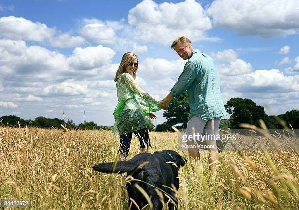 Couple with dog in field