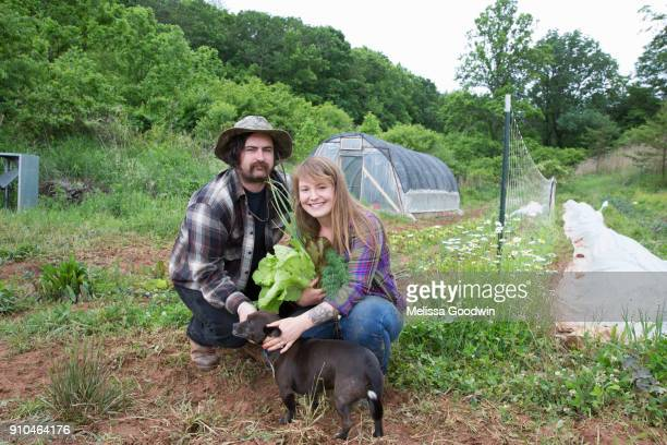 Couple with dog in vegetable garden looking at camera smiling