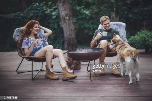 ポーチの上に犬とカップルします。 - ミッドアダルト ストックフォトと画像
