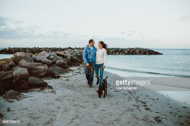 Couple with dog walking at the beach