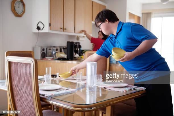 pareja con síndrome de down aprender cocinar verduras corte - discapacidad intelectual fotografías e imágenes de stock