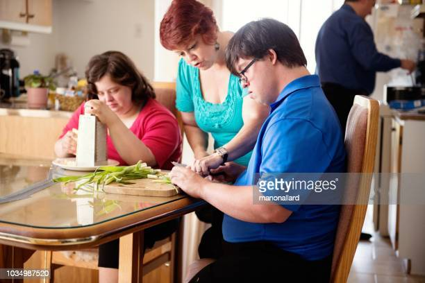 couple with down syndrome learning cooking cutting vegetables - independence stock pictures, royalty-free photos & images