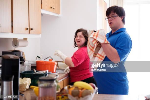 couple with down syndrome washing the dishes - crockery stock pictures, royalty-free photos & images