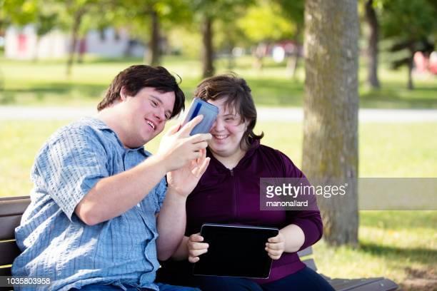pareja con síndrome de down que trabaja haciendo selfie con teléfono móvil - discapacidad intelectual fotografías e imágenes de stock