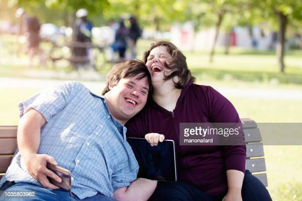 couple with down syndrome working doing selfie with mobile phone - down syndrome stock pictures, royalty-free photos & images