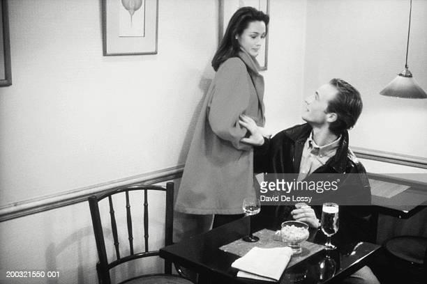 couple with drinks at restaurant, man looking at woman (b&w) - heteroseksueel koppel stockfoto's en -beelden