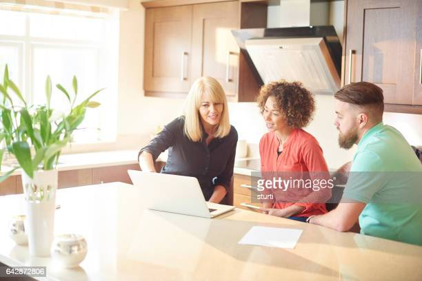 couple with estate agent looking at deals