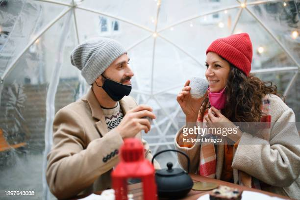 couple with face mask dining in plastic igloo dome tent outside cafe. - coronavirus winter stock pictures, royalty-free photos & images