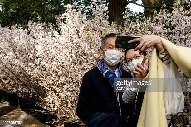 A couple with face masks as a preventive measure taking selfies during the corona virus pandemic Although the government had suggested no gatherings...
