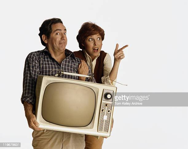 couple with facial expression holding old television - 1982 stock pictures, royalty-free photos & images