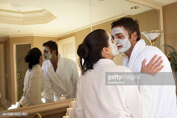 Couple with facial masks kissing in bathroom