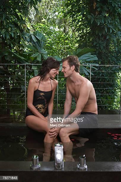 Couple with feet in bath on terrace