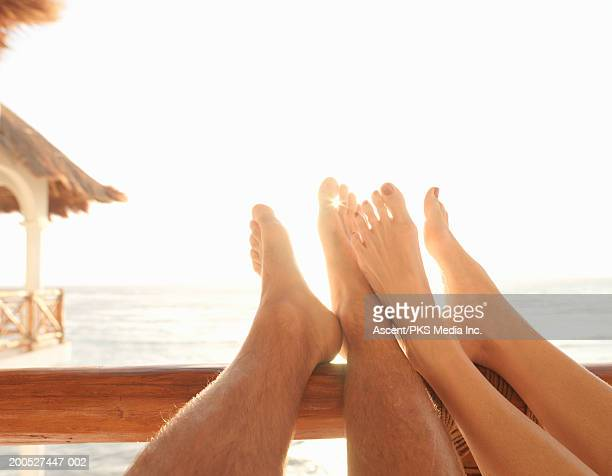Couple with feet on railing with ocean behind, low section