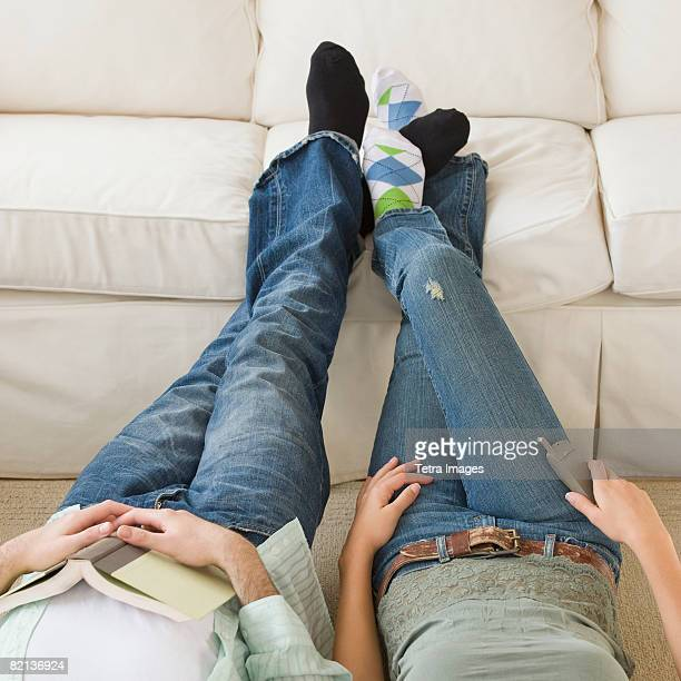 couple with feet up on sofa - playing footsie stock pictures, royalty-free photos & images