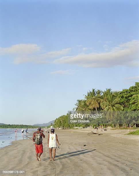 couple with fishing rods walking on beach, rear view - playa tamarindo fotografías e imágenes de stock