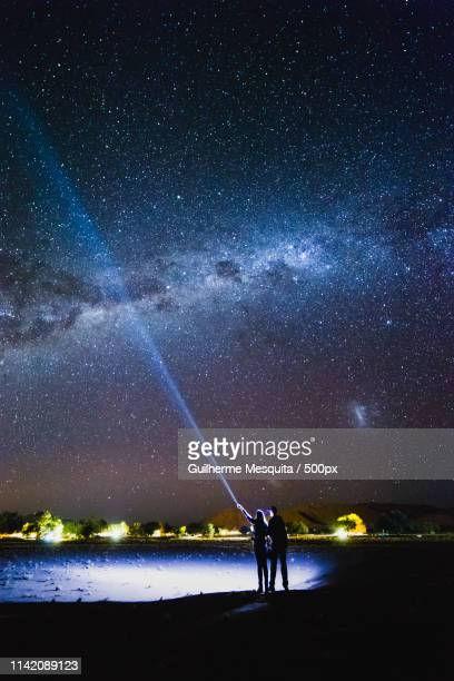 couple with flashlight pointing to the galaxy at the sky milky - セスリエム ストックフォトと画像