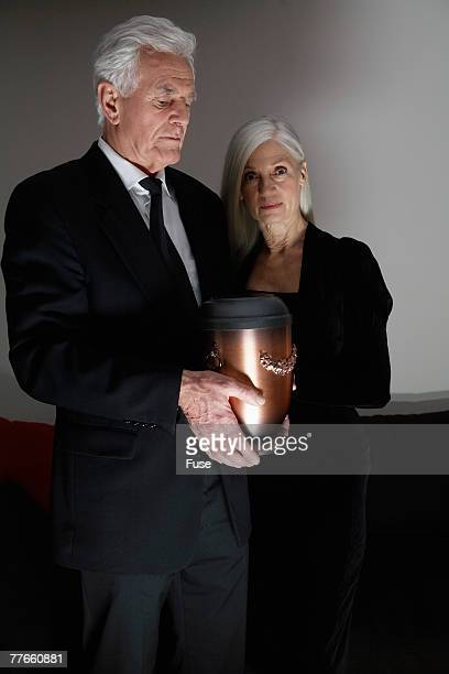 couple with funeral urn - urn stock pictures, royalty-free photos & images