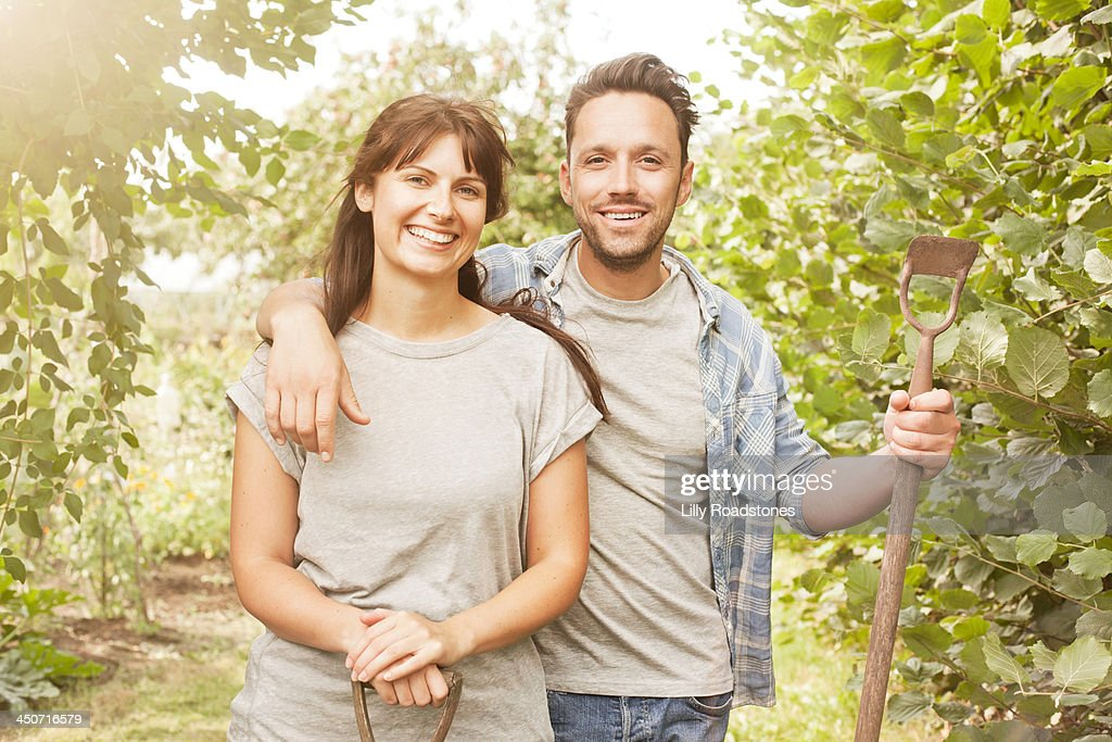 Couple with gardening tools at allotment entrance : Stock Photo