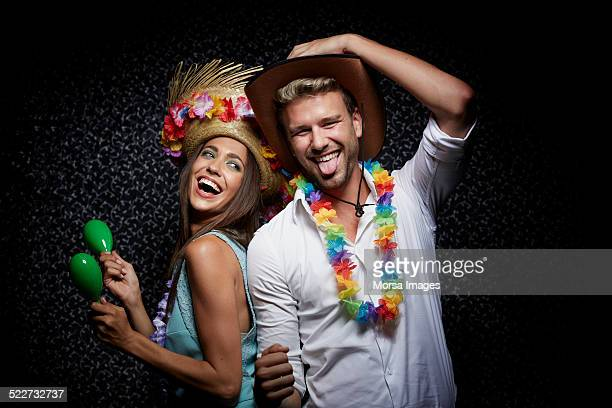 couple with garlands and maracas in nightclub - maraca stock photos and pictures