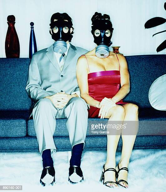 couple with gas masks sitting on couch (cross-processed) - feticismo foto e immagini stock