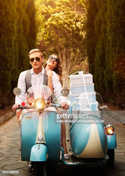 Couple with gift boxes driving vintage scooter