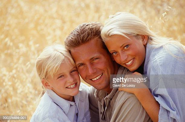 Couple with girl (8-9 years) in field, portrait