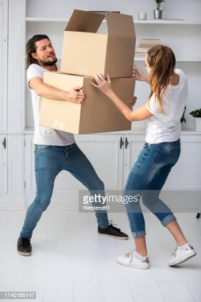 couple with girlfriend carrying cardboard boxes in new home - oggetti pesanti foto e immagini stock