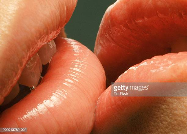Couple with glossy lips kissing, close-up
