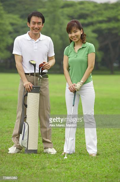 Couple with golf club and golf bag, smiling at camera
