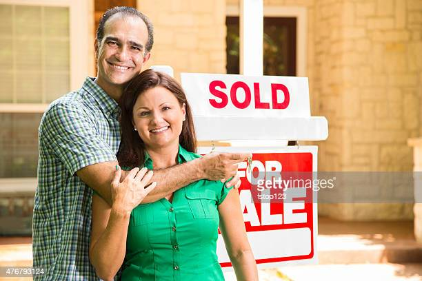 Couple with 'house for sale, sold' real estate sign. Home.