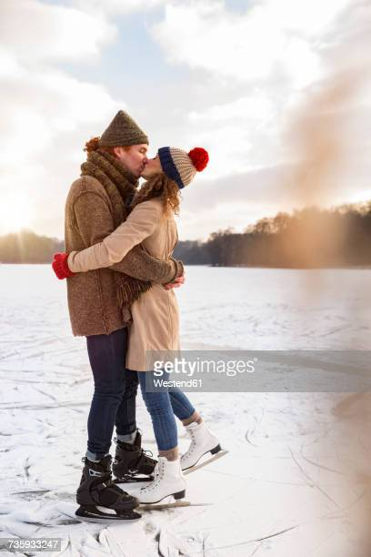 Couple with ice skates kissing on frozen lake