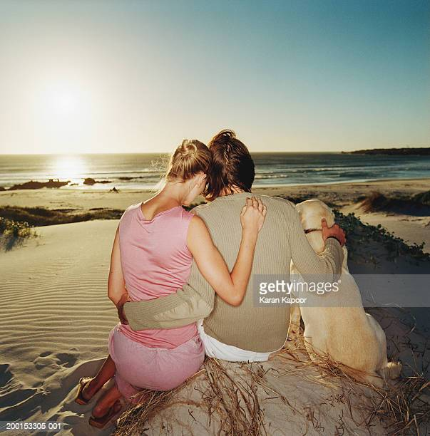 Couple with labrador, embracing on beach, sunset, rear view