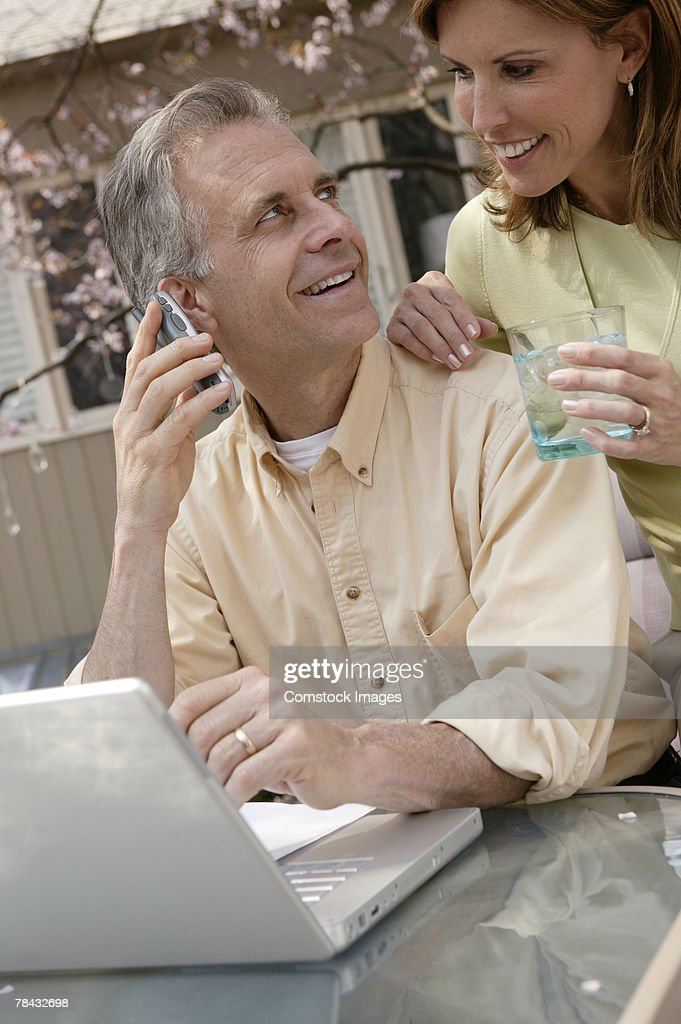 Couple with laptop and cell phone : Stockfoto