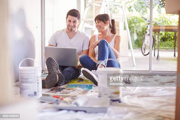Couple with laptop having a break from renovating new home