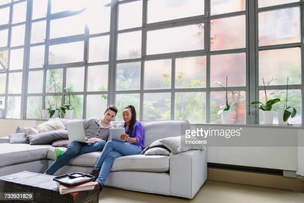 couple with laptop sitting on sofa talking - florence douillet photos et images de collection