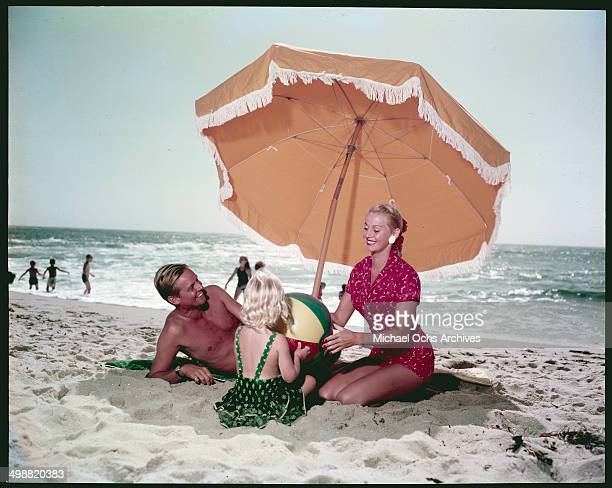 A couple with little girl rests and play with a beach ball under a beach umbrella on La Jolla beach in La Jolla California in June 1952